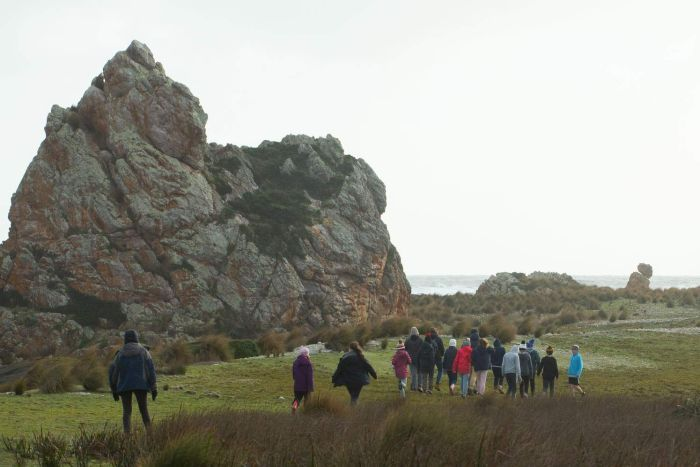 School group walks past huge rocky landmark