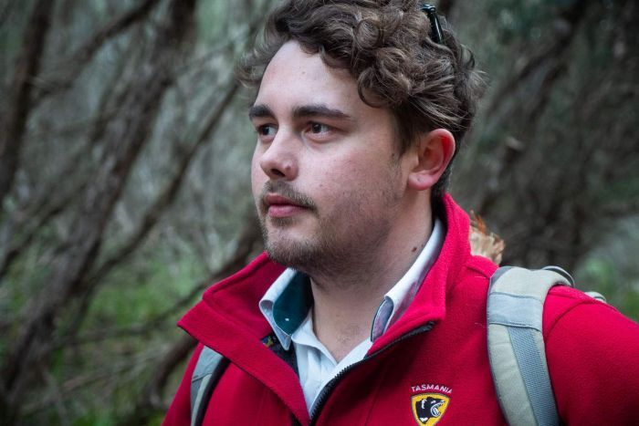 a portrait of Jye Crosswell in red parks and wildlife jacket under a ti-tree canopy on the walk into King's Run