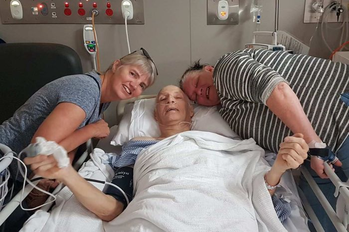 Allan Mayo-Smith smiles from a hospital bed surrounded by his two daughters.