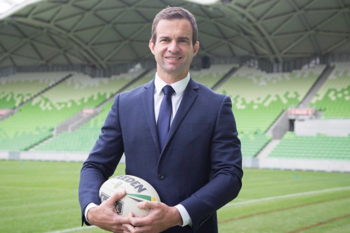 Sport CEO holding a football and looking at the camera