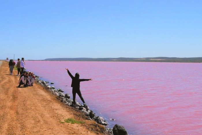 Chinese tourist poses for photo at the Pink Lake in Port Gregory
