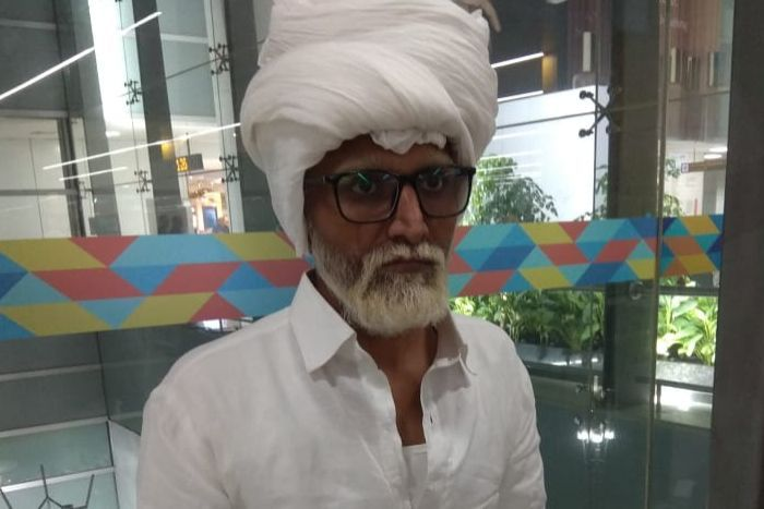 A man who appear to be an elderly, dressed in white, with a white beard and turban.
