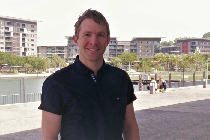 A man with brown hair and a black shirt stands outside. There are buildings and water behind him.