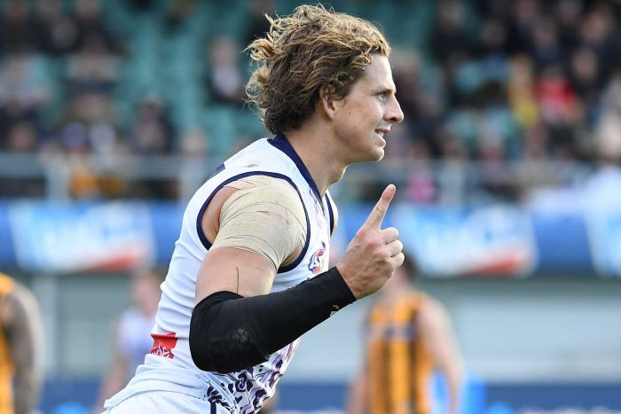 A side-on shot of Dockers captain Nat Fyfe celebrating a goal during an AFL game with his finger raised.