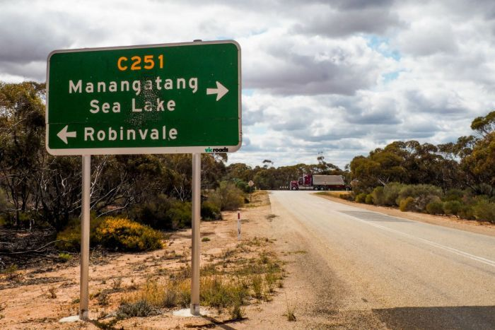 The C251 Robinvale-Sea Lake road sign with a truck driving in the background.