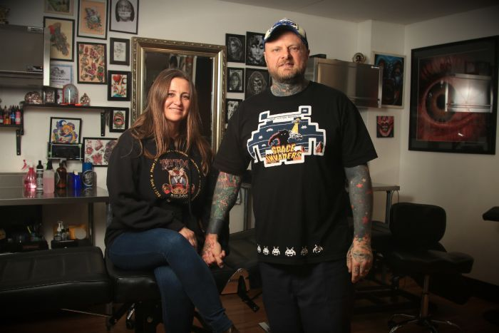 Lance Daly holds the hand of his wife Rebecca inside their tattoo shop.