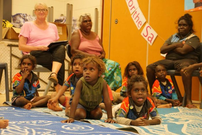Small Aboriginal children in classroom on mat with adults sitting in chairs