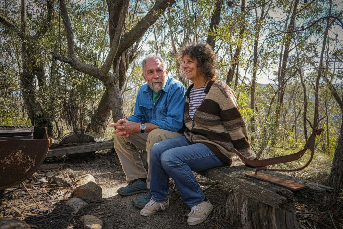 Rolley Clarke and Robin sitting on a wooden seat, just metres from their Mt Victoria home