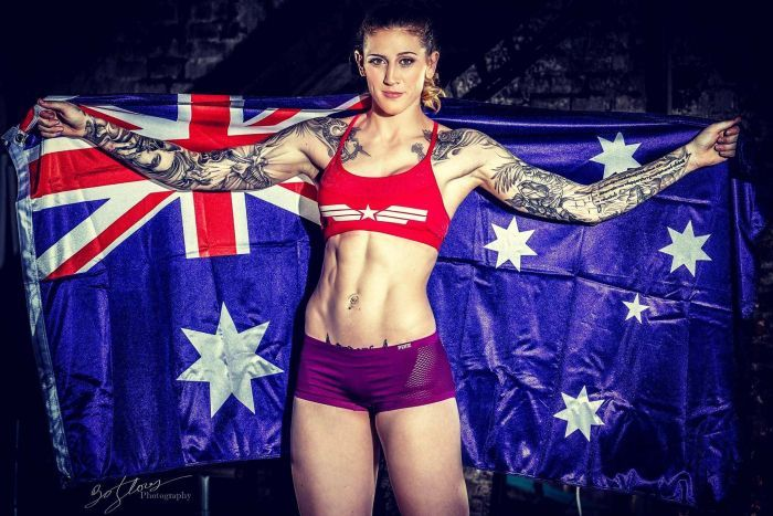 UFC fighter Megan Anderson has arms spread holding an Australian flag.