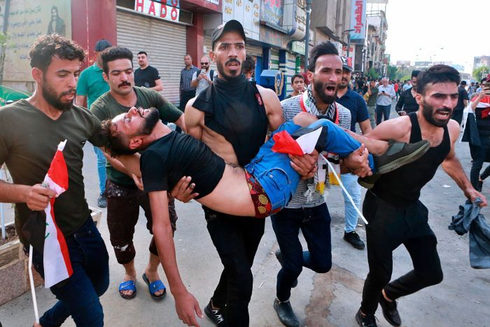 An injured protester is carried in Iraq by fellow protesters as they scream.
