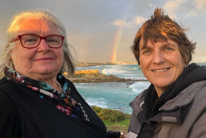 Two women stand near a bay with a rainbow behind them.
