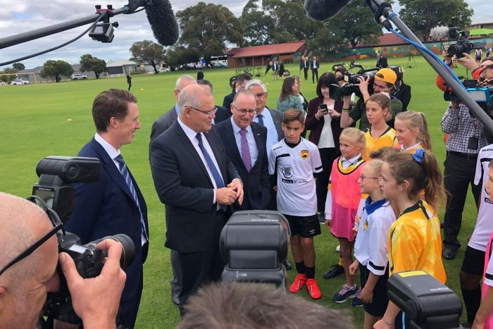 Politicians in suits stand in front of cameras and children in a football field