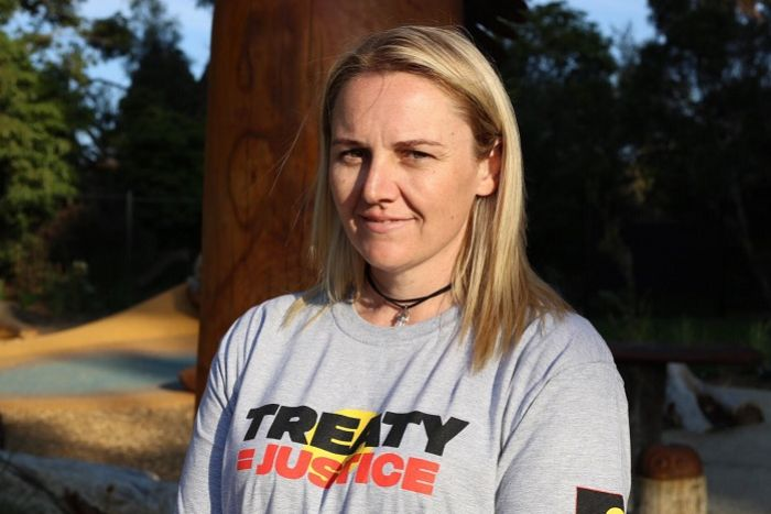 "Fiona Newson is dressed in a T-shirt reading ""Treaty = Justice"" as she stands in front of a park."