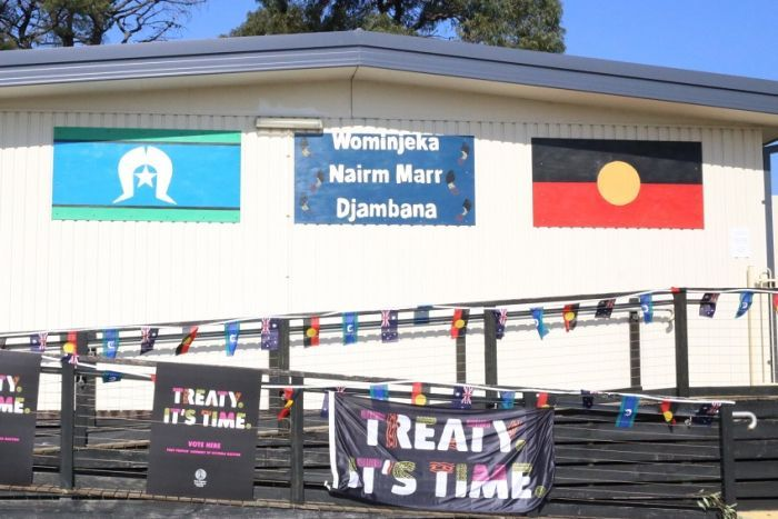 The Aboriginal and Torres Strait Islander flags are pinned to the outside of a shed beside a sign reading 'Wominjeka'.