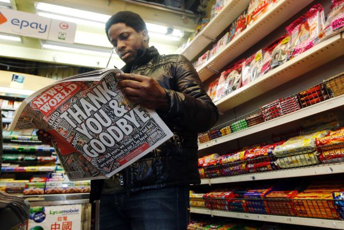 A man stands in a newsagents reading the News of the World newspaper in front of store shelves
