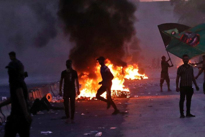 Anti-government protesters set fires as they rally on a closed Baghdad street. Smoke fills the air.