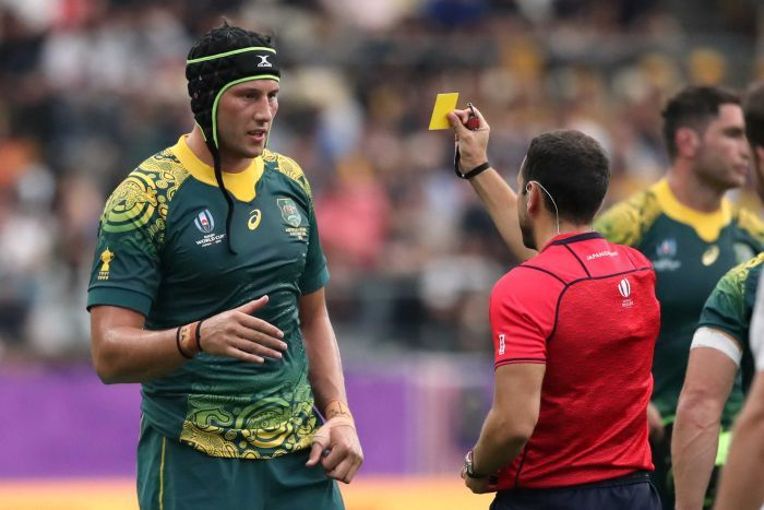 A Wallabies player wearing headgear is shown a yellow card from the referee at the Rugby World Cup.