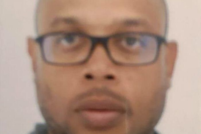 Mickael Harpon stares at the camera blankly. The photo is a close up of his face and appears to have been taken for a passport.