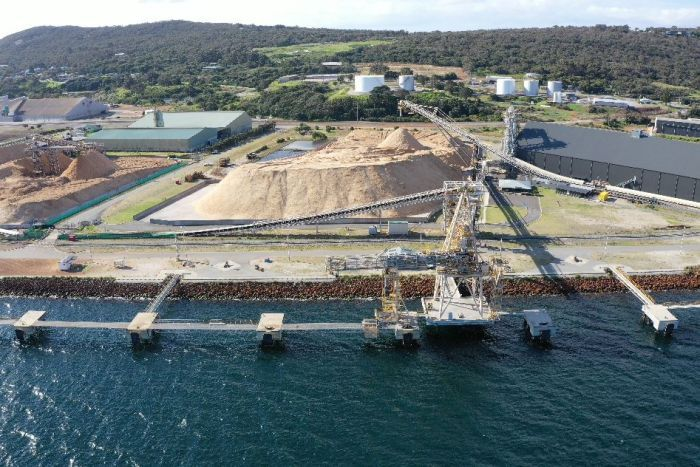 A drone shot showing a woodchip pile next to a port.