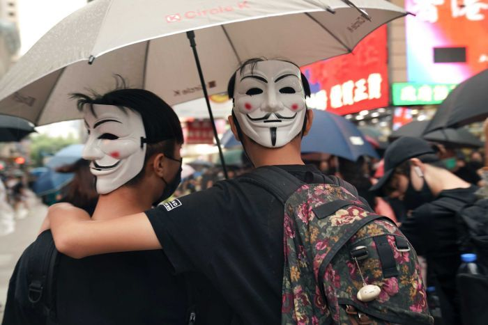 Protesters wearing banned face masks