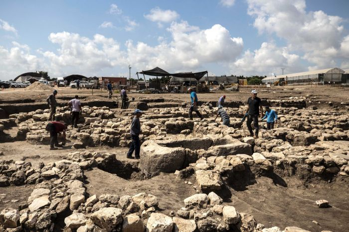 A group of archaeologists stand on and dig out large piles of rock and soil.
