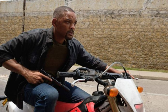 Will smith in daylight on motorbike holding gun, wall in background.