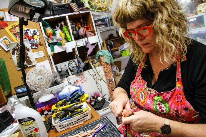 A woman in her artist studio surrounded by toys
