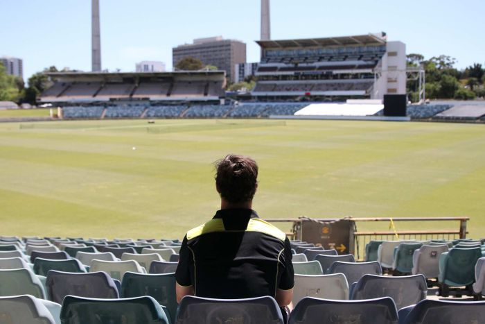 A wide shot of Hilton Cartwright sitting in the stands at the WACA Ground with his back to the camera looking out over the oval.