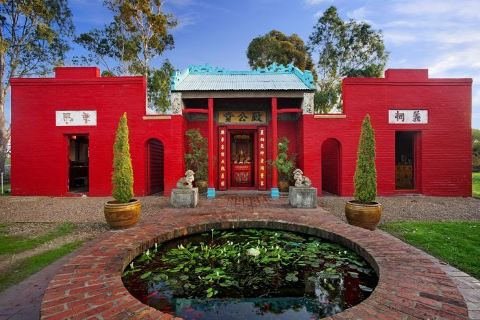From a low angle, you look across a red brick water feature that shows Bendigo's bright read Joss House Temple.