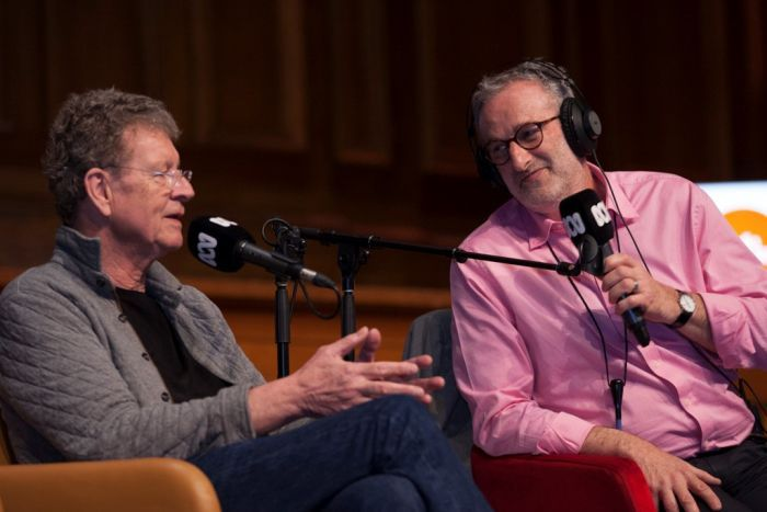 Red Symons and Jon Faine sit side-by-side on stage as they speak into ABC microphones.