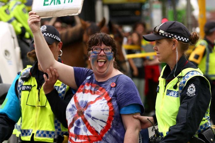 An Extinction Rebellion protester being arrested by police holding up a protest sign.