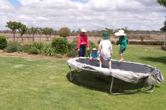Three children bounce on a trampoline in broad brimmed hats
