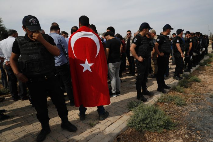 Turkish police officers secure the area as a Turkish flag-draped mourner attends a funeral.