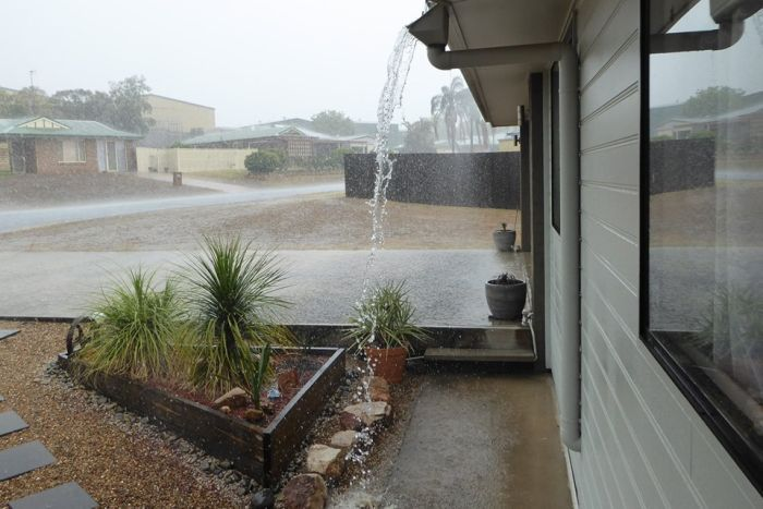 Rain pours out of the downpipe of a home at Gatton.