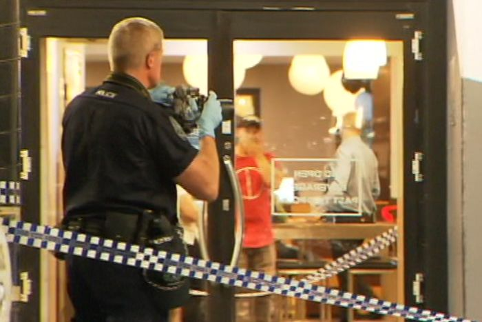 A police officer taking a photograph of a glass door with crime tape behind him
