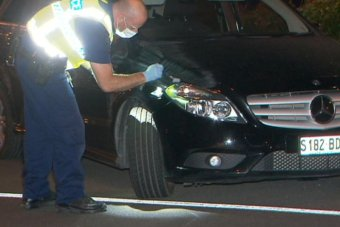 A police officer dusts a black car with a soft brush