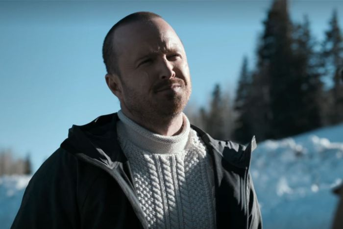 A man squints while rugged up in the Alaskan wilderness with snow on the ground.