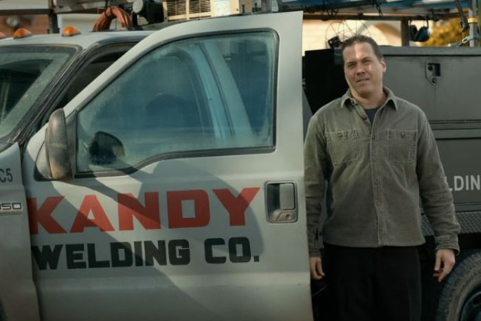 """A man stands next to a truck with the words """"Kandy Welding Co"""" on it."""
