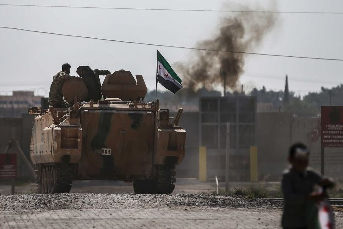 Syrian opposition fighters on an armoured personnel carrier in front of smoke