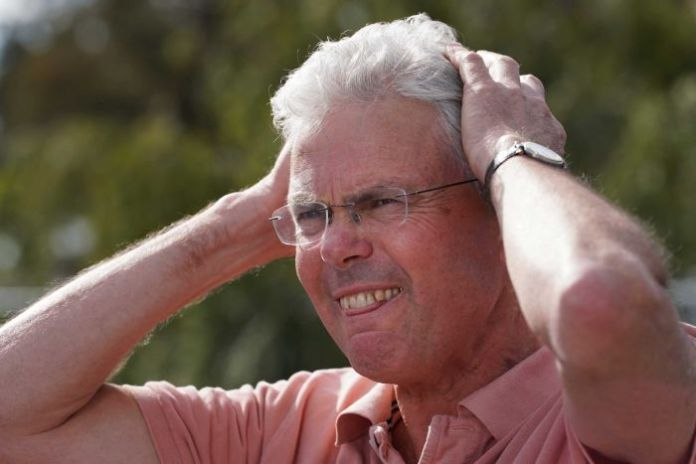 A racehorse trainer grimaces in disbelief as he puts both hands to his head in frustration.