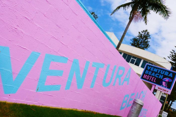 pink wall with Ventura Beach written across it, and a retro sign of the motel