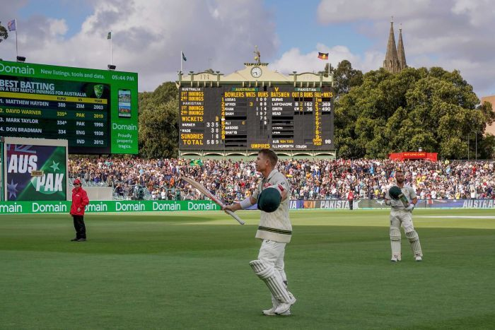A cricketer raises his bat as he walks off Adelaide Oval with the scoreboard in the background.