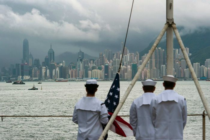 Three US Navy soldiers in white are seen out of focus onboard a ship as they look across the harbour to Hong Kong's skyscrapers.