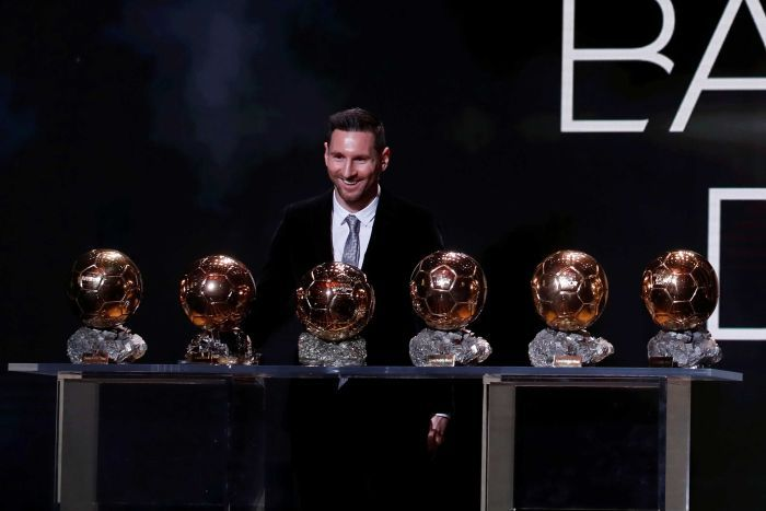 Lionel Messi stands smiling over six Ballon d'Or trophies.
