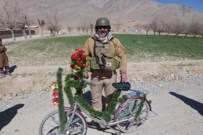 A middle-aged man in combat vest, smiling, with a decorated bicycle.