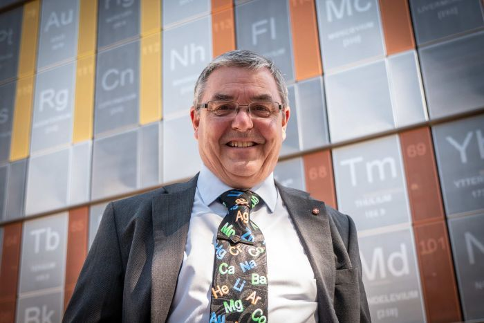 A university professor with grey hair and glasses, smiling at the camera standing in front of a large periodic table.