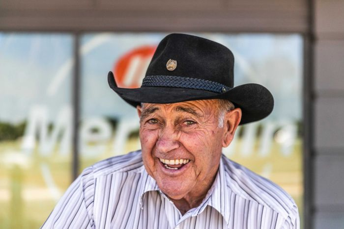 An old man with a cowboy hat on smiles at the camera.