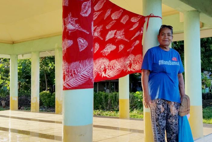 A woman in Samoa stands beside a red flag, put up near the front of a property to let medical teams know they need vaccinations.