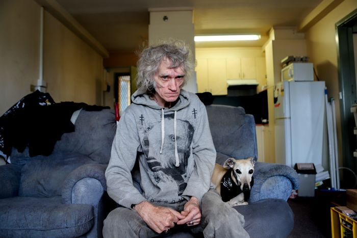 Man with grey jumper and grey hair sits on blue couch next to dog, with apartment kitchen in background