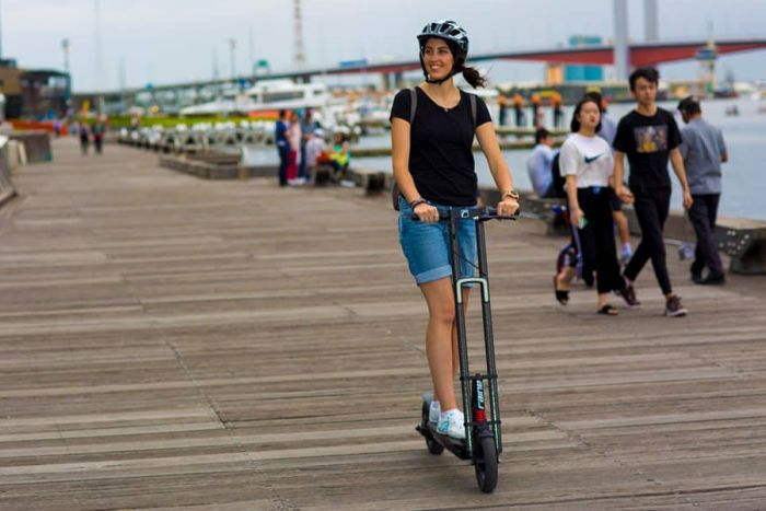 Michelle Mannering rides an e-scooter on a wharf wearing a helmet and smiling on a grey day.